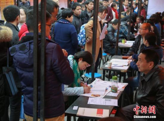 資料圖:在武漢市納傑人才市場招聘會上,擠滿了前來應聘的求職者。中新社記者 張暢 攝
